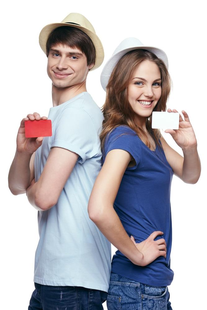 Zwei junge Menschen halten zufrieden eine kostenlose Kreditkarte in der Hand